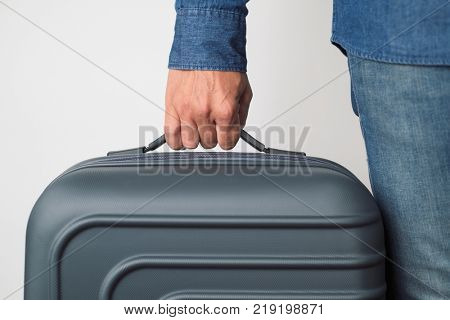 closeup of a young caucasian man carrying a suitcase by its handle against an off-white background