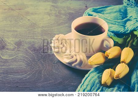 Fresh delicious white meringue cookies and cup of hot tea with yellow tulips on vintage wooden table. Women's day or mother's day consept. Spring time.