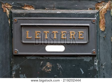 Vintage letters slot. A dark gray Letters slot on a shabby wooden door.