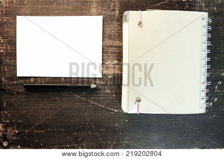 a blank white postcard with a black pencil and a white blank agenda next to it on a wooden plank background