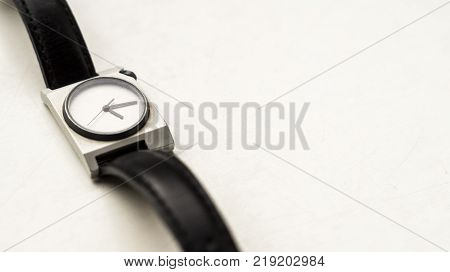 A wrist watch timer with black straps on a white background