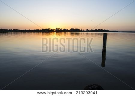 a beautiful sundown/sunset over a lake with a bright yellow sun behind the trees in the distance