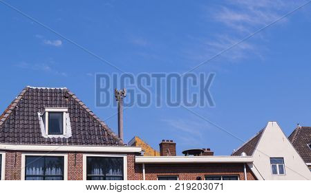 traditional old Dutch rooftops with orange and grey colours on a clear blue summer sky. Leiden, Netherlands