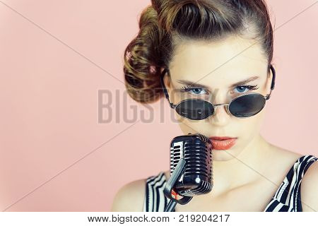 Pin up young girl on pink background radio. Beauty and vintage fashion. Music look and retro style pinup. Woman singer with stylish retro hair and makeup. Girl in glasses sing in microphone.