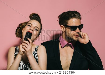 Pinup girl and man on pink radio. Music and love security. Beauty vintage fashion music band. Singer man and woman with retro hair and makeup. Couple in love in glasses sing in microphone. poster