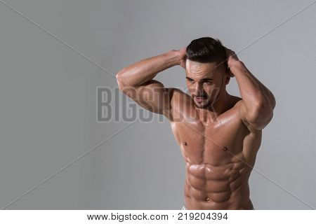 Man with muscular wet body and torso. Dieting and fitness. Athletic bodybuilder man on grey background. Sport and workout. Coach sportsman with bare chest copy space