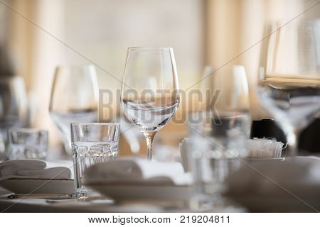 In The Restaurant There Are Wine Glasses In The Center Of The Composition, Cutlery, Napkins And Othe
