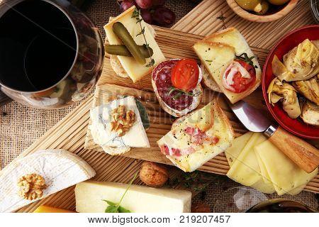 Italian antipasti wine snacks variety set. Cheese Mediterranean olives pickles Prosciutto di Parma tomatoes artichokes and wine in glasses. Spanish tapas