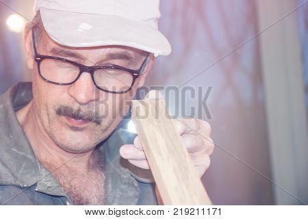 Carpenter in glasses checks the Board. Selective focus