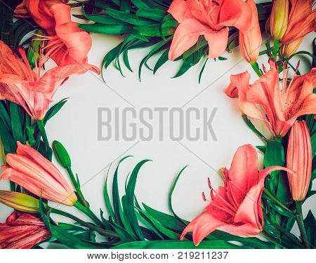 Exotic Flowers composition. Wreath frame made of pink lily flowers on the white background. Art exotic summer concept. Vintage filter effect. Top view flat lay. Selective focus space for text