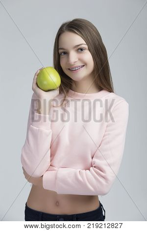 Dental Concepts. Portrait of Happy Teenage Female With Teeth Brackets. Posing With Green Apple and Smiling Against White.