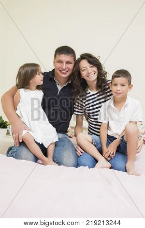 Family Ideas. Happy caucasian Family of Two Parent and Two Kids Sitting Together Embraced and Smiling Happily. Vertical Image Orientation
