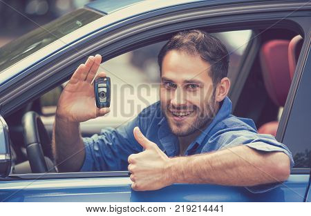Happy smiling young man sitting in his new blue car showing keys thumbs up isolated outside dealership lot. Personal transportation purchase concept