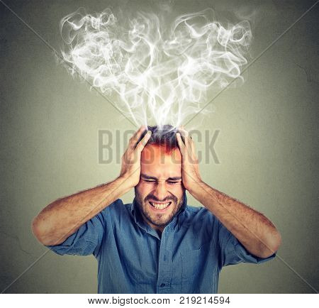 Portrait young stressed man screaming thinking too hard steam coming out up of head isolated on grey wall background. Face expression emotion perception