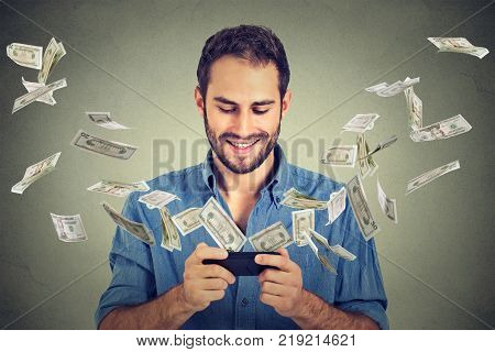 Technology online banking money transfer e-commerce concept. Happy young man using smartphone with dollar bills flying away from screen isolated on gray wall office background.
