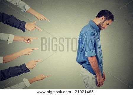 Concept of accusation guilty person guy. Side profile sad upset man looking down many fingers pointing at his back isolated grey office wall background. Negative human face expression emotion feeling