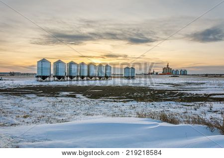 Metall barns and granaries in the snowy winter field at sunset of the day