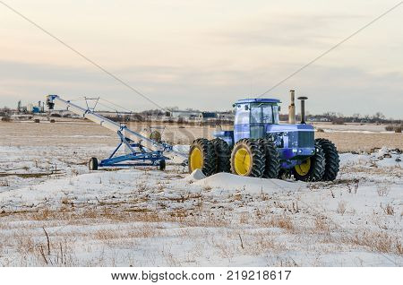Green tractor and grain loader on the snow field. Grain storage and elevator on the background.