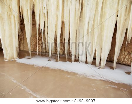 Strange and mysterious giant icicles, resembling a pipe organ or stalactites, hang from the arch of sandstone and hit an icy surface of a frozen lake. A flooded sand quarry in winter. View from above