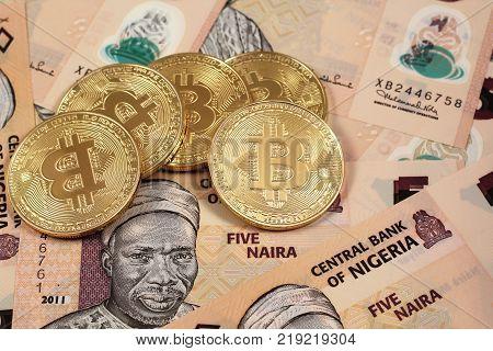 A close up image of golden bitcoins close up with Nigerian naira notes