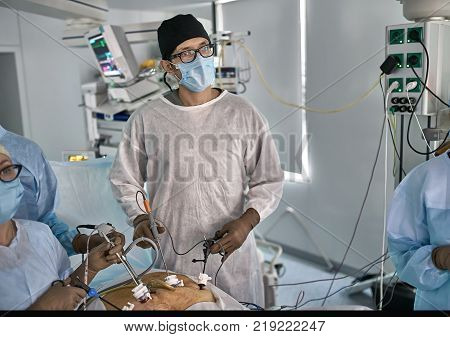 Surgeon with assistants are using laparoscopy cameras inside the patient's abdominal during the operation. There are medical equipment with an EKG monitor behind them. Horizontal.