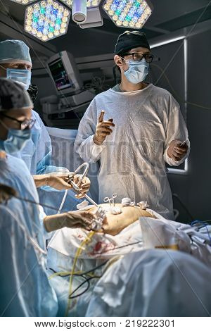 Team of surgeons are using laparoscopy cameras inside the patient's abdominal during the operation. There is an EKG monitor behind them. Vertical.