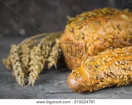 Freshly made baguette and a loaf of bread from wheat flour with ears of wheat on a rustic table. Background of ripe wheat ears.