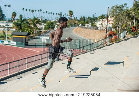 Muscular Jamaican athlete gaining momentum while sprinting up steps of stadium stairs.
