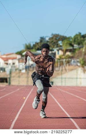 Muscular Jamaican athlete leaning forward for momentum while sprinting in lane on stadium track.