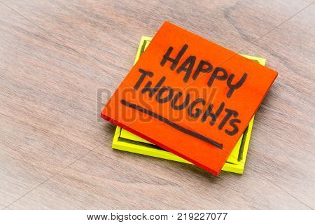 happy thoughts inspirational reminder - handwiriting on a sticky note against grained wood