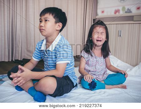 Quarreling conflict of children. Asian girl has problem between brother and scream crying with tears sadden boy sitting near by. Relationship difficulties in family concept.