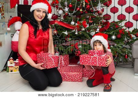 Cheerful Mother And Son Holding Christmas Presents And Posing In Their Home