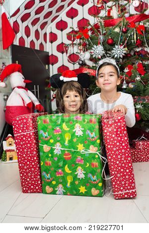 Boy And Girl With Christmas Gifts In Front Of Christmas Tree In Their Home