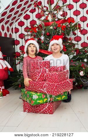Cheerful Two Kids With Many Presents In Front Of Tree In Their House