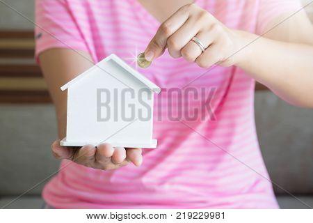 women hand putting money coin in piggy bank Saving money concept concept of financial savings to buy a house Growth business money.