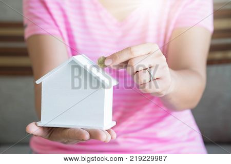 women hand putting money coin in piggy bank Saving money concept concept of financial savings to buy a house Growth business money.