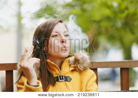 Beautiful Happy Caucasian Young Smiling Brown-hair Woman In Yellow Coat Smoking Cigarette In Outdoor