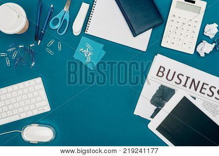 top view of digital tablet with blank screen cup of coffee calculator and office supplies on black