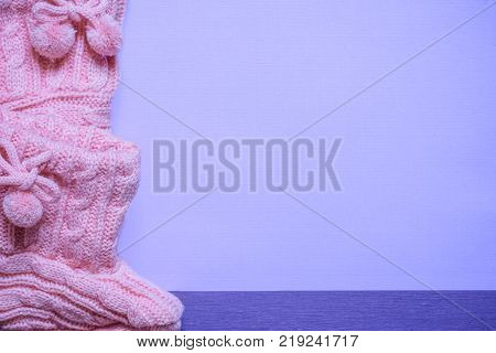Knitted pink bootees on purple background - Little pink handmade bootees displayed on a blank purple paper with place for text on a purple wooden table. A birth announcement message card idea.