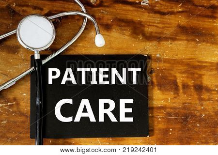 Patient Care word written on mini board with stethoscope on wooden background