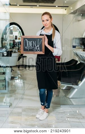 blonde owner of salon standing with sign open and looking at camera