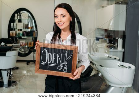 smiling brunette owner of salon standing with sign open