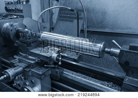 The lathe machine cutting the steel rod in the light blue scene.The manual lathe machine with the steel bar.