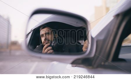 Young private detective man sitting inside car and photographing with slr camera