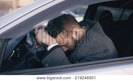Young bearded business man sitting in car very upset and stressed after failure and moving in traffic jam