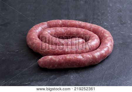 Rolled uncooked botifarra or Catalan sausage. Isolated over black slate
