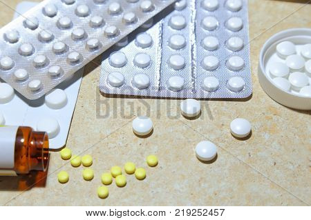 Various tablets - analgesics antidepressants vitamins antiviral drugs scattered on the table.