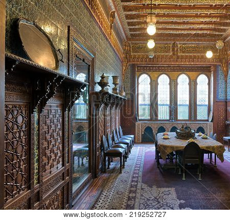 Cairo Egypt - December 2 2017: Manial Palace of Prince Mohammed Ali. Dining room at the Residence Building with ornate wall and ceiling Big ornate window built-in and wooden decorated cupboards