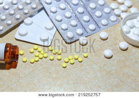 Various tablets - analgesics antidepressants vitamins antiviral drugs scattered on the table.