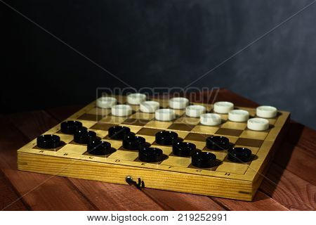 Chess board with chess on a wooden black table. Beautiful dark background Hobby. Checkers on the playing field for the game.